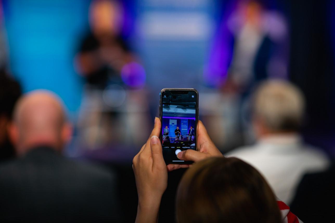 Kuvassa on älypuhelin, jolla kuvataan foorumin ohjelmaa.