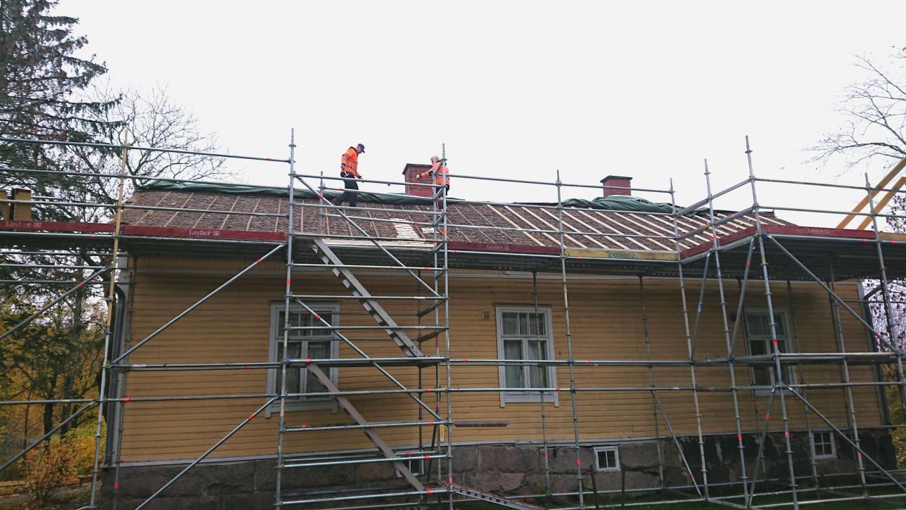 Kuralan Vähä-Rasin tiilikaton korjaus meneillään. Rakennustelineitä, korjaajia katolla. Kuva: Turun museokeskus