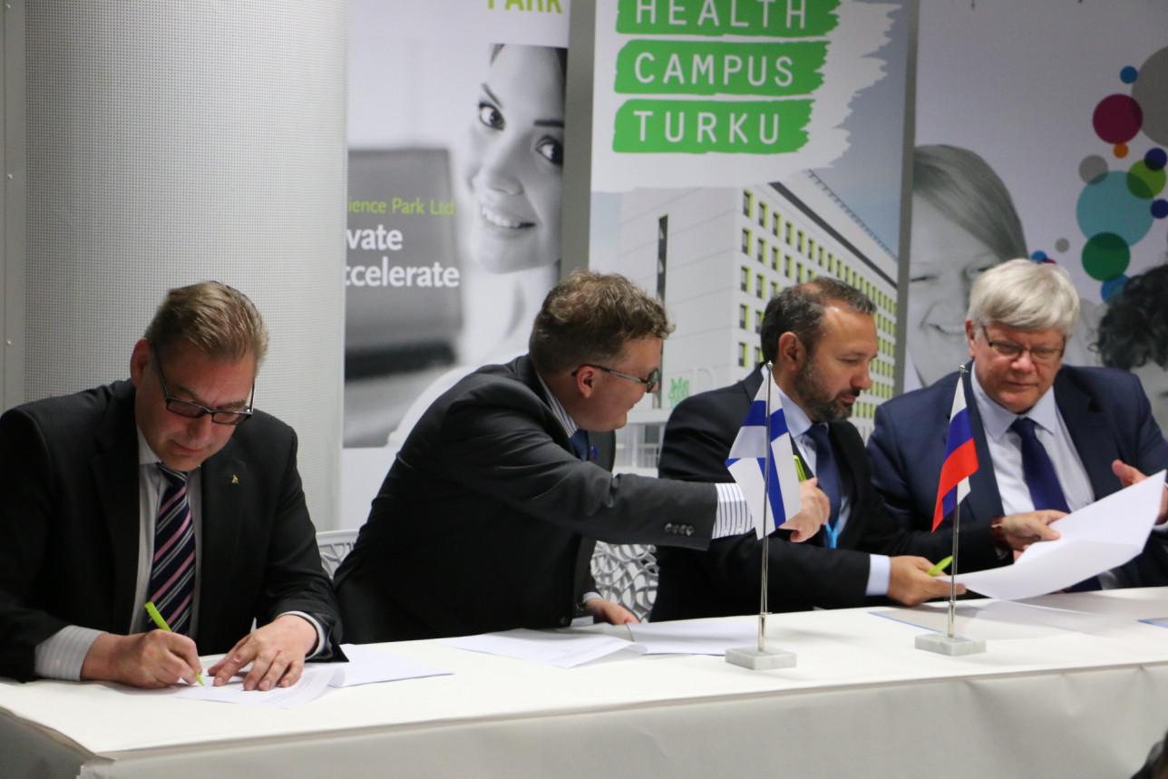 Toimitusjohtajat ja rehtori allekirjoittavat sopimuksen pöydän ääressä.