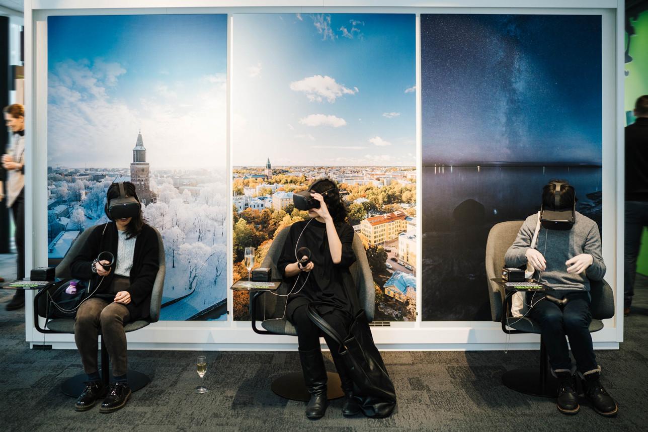 Näyttelyvieraat katsovat 360-kuvia VR-lasit päässä.