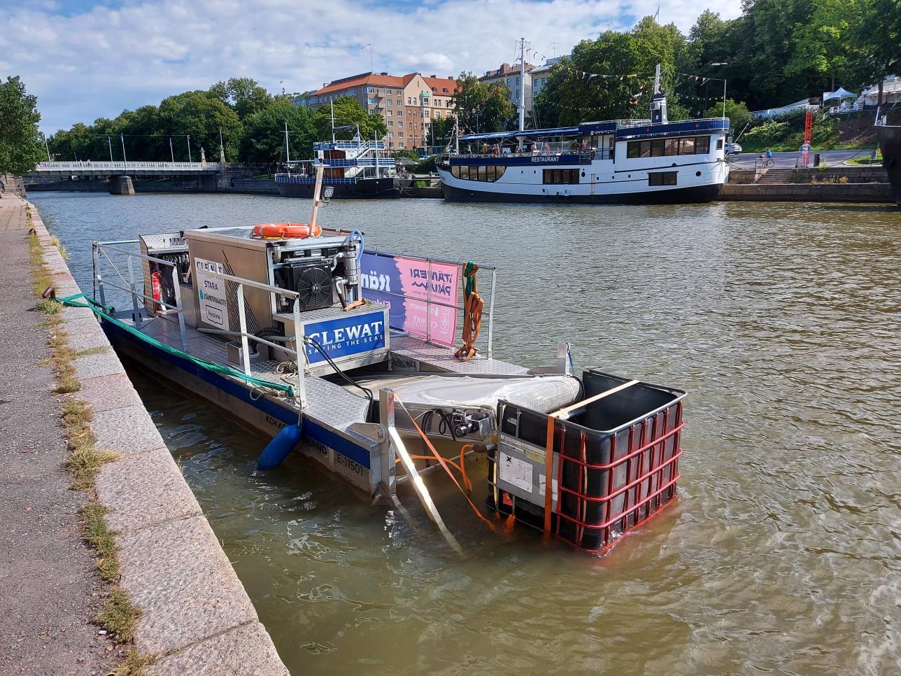 Cleansweep-alus Aurajoella. Aluksen perässä on liukuhihnamainen laite, joka kerää roskaa erilliseen astiaan. Aluksen kyydissä on kaksi ihmistä.