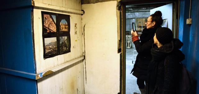 Kaksi naishenkilöä tutkii seinässä olevia yksityiskohtia.