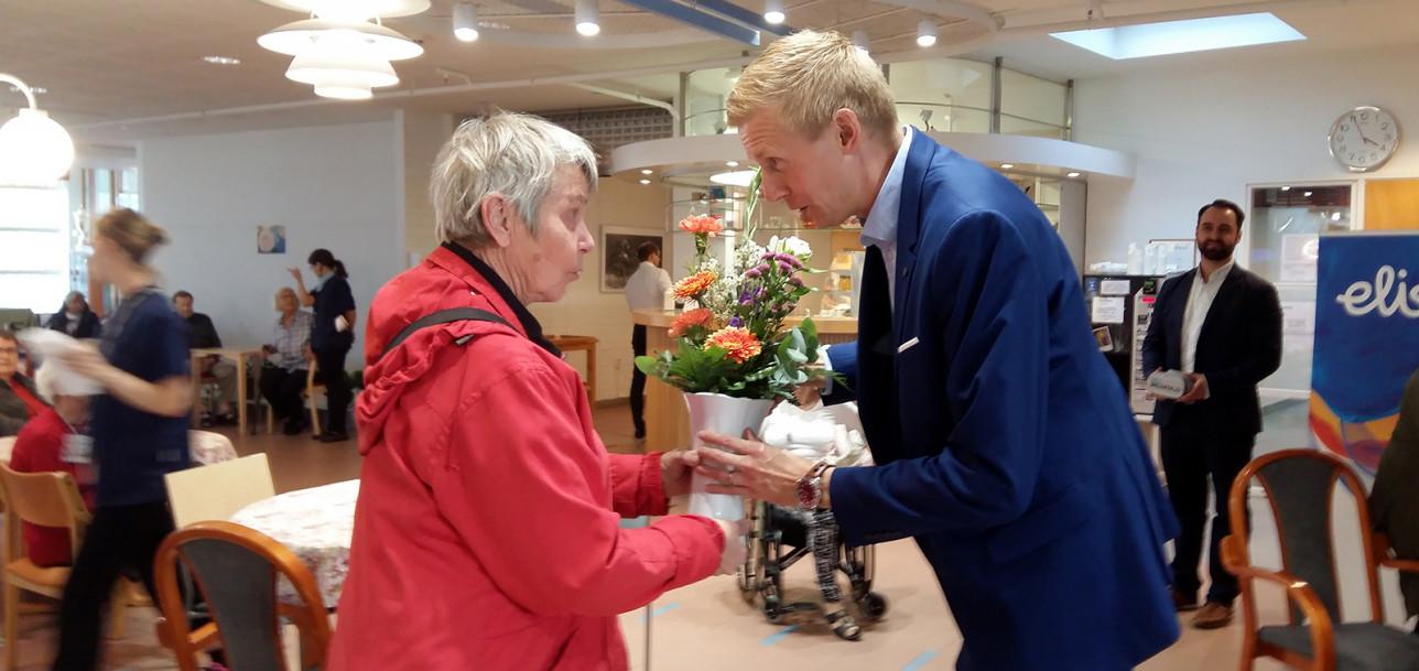 Elisan aluejohtaja Juha Laukkanen lahjoittaa kukat arvonnan voittajalle.