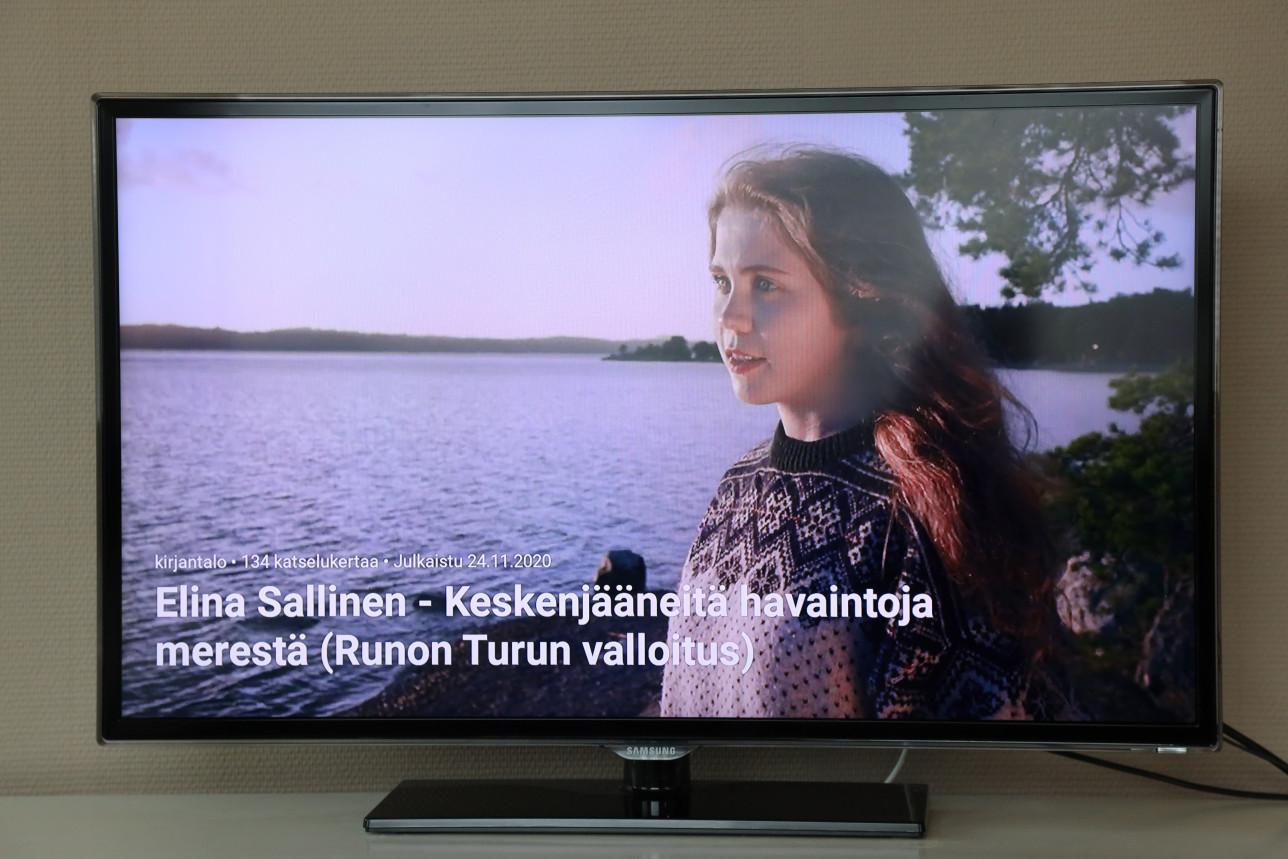 Television ruudulla näkyy runoilija Elina Sallinen Ruissalossa meren rannalla.