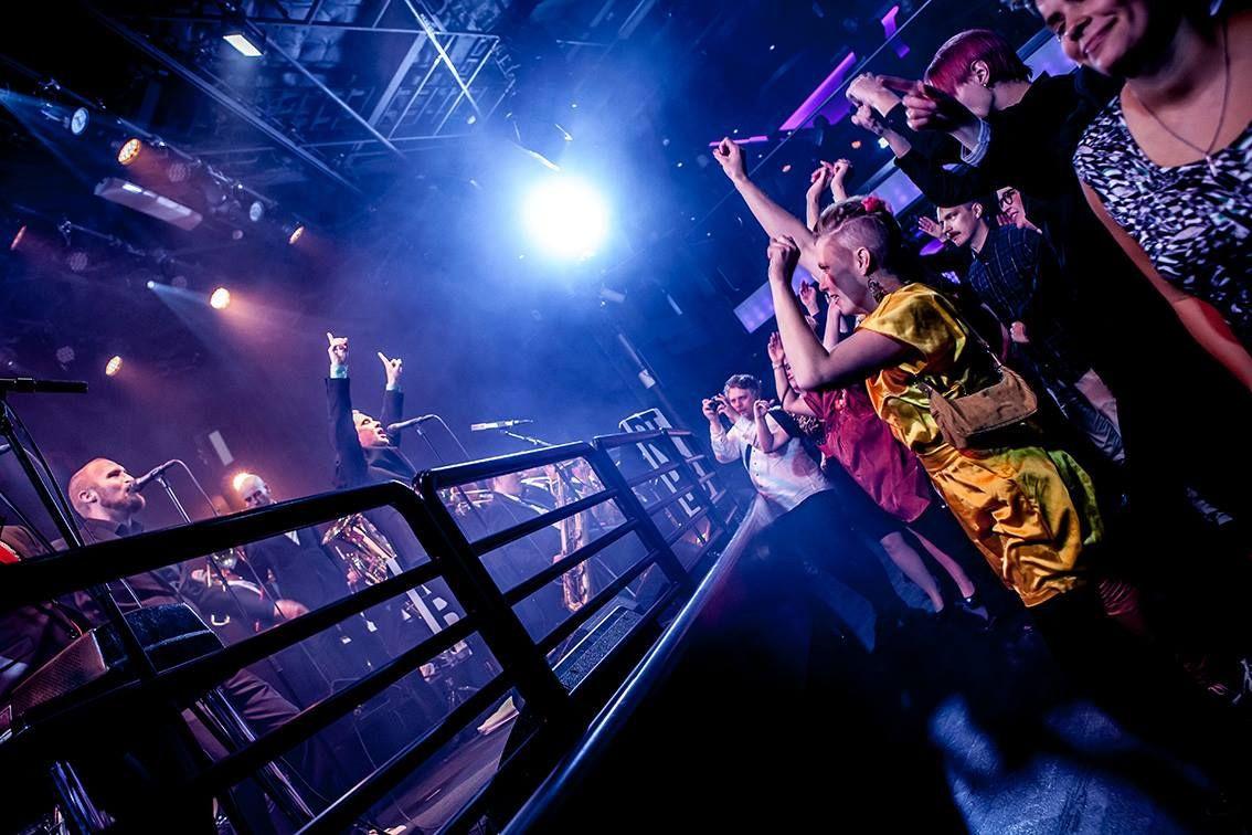 Bändi soittaa lavalla ja lavan edessä ihmiset tanssivat.
