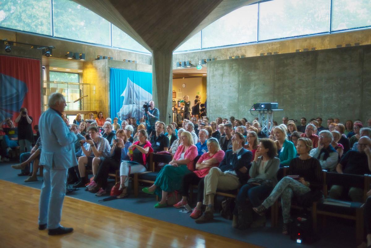 Peter Greenaway luennoi luentosalissa ja kymmenet ihmiset seuraavat luentoa istuen penkeillä