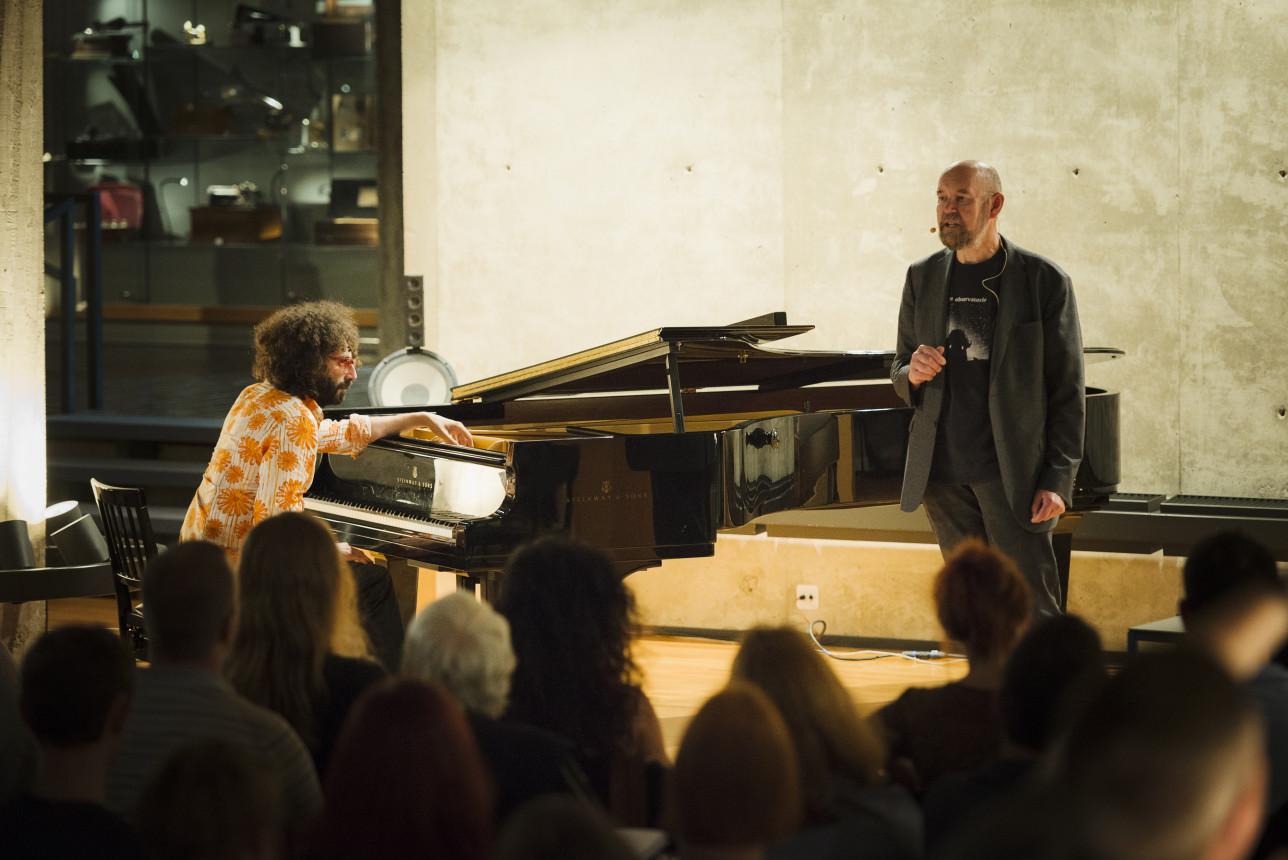 Fabrizio mocata istuu flyygelin edessä lavalla ja Esko Valtaoja seisoo vieressä puhumassa