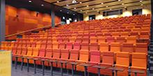 Auditorio, jonka penkit on verhoiltu punaisella kankaalla.