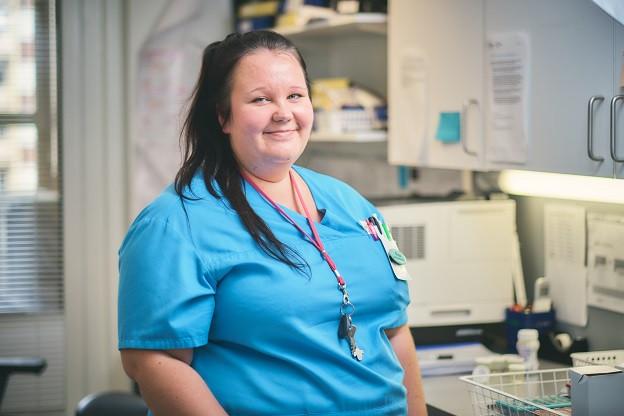 Sairaanhoitaja istuu työpisteellään