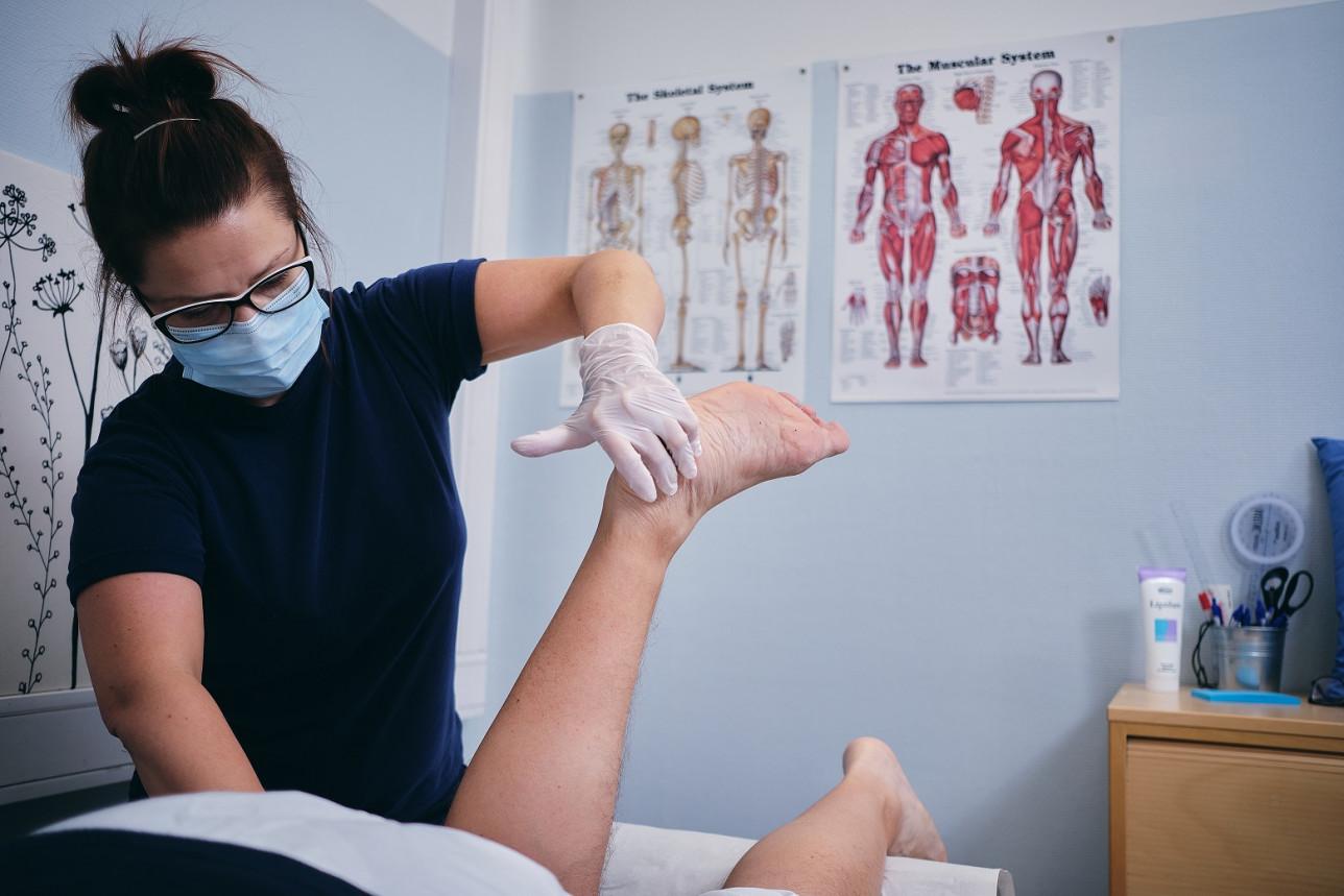 Fysioterapeutti taivuttaa kuntoutettavan asiakkaan jalkaa