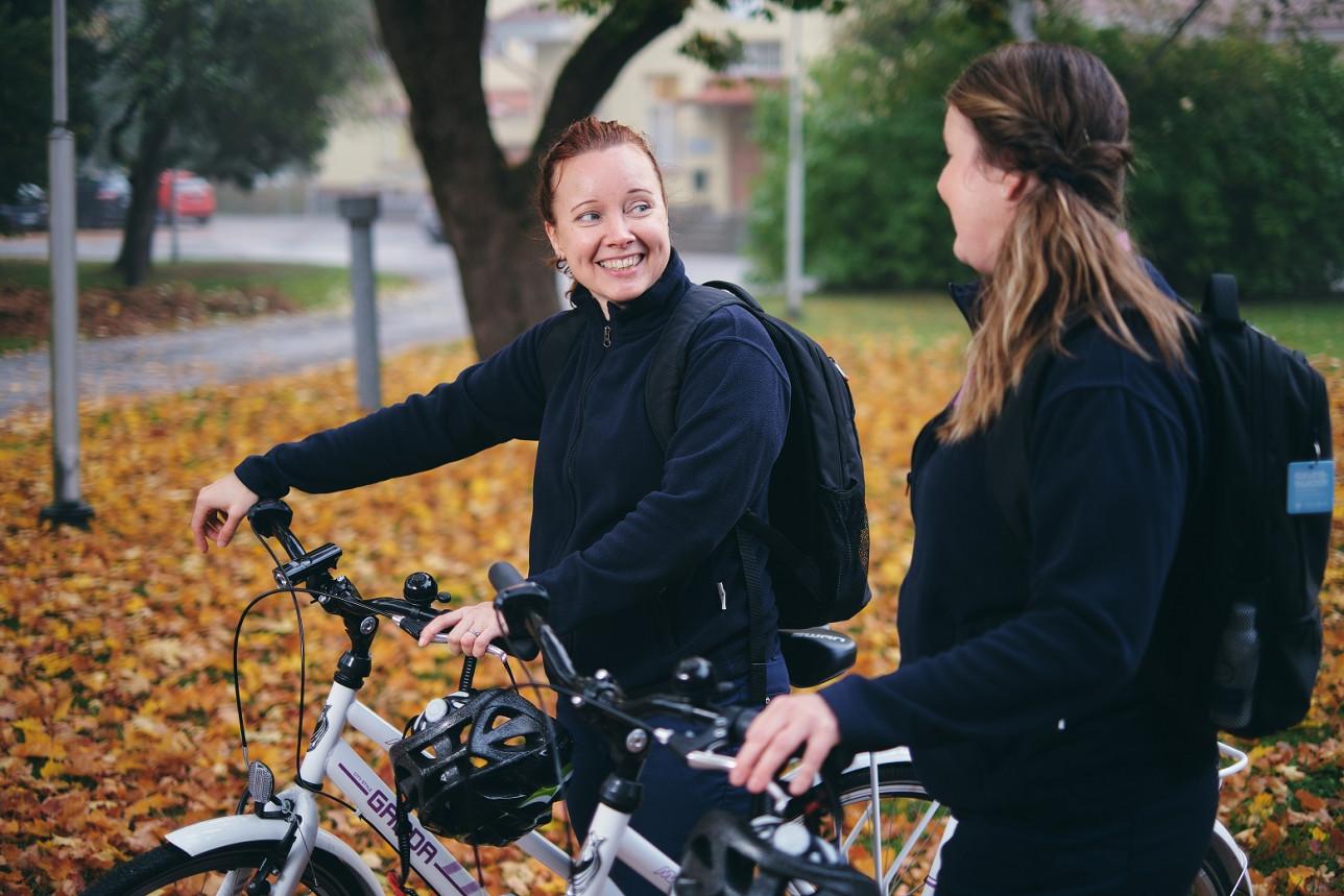 kaksi polkupyöriensä kanssa seisovaa naista juttelee keskenään syksyisessä ilmassa ulkona