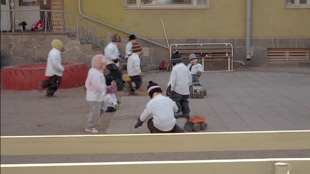 Valkoiseen puettuja lapsia leikkii päiväkodin pihalla