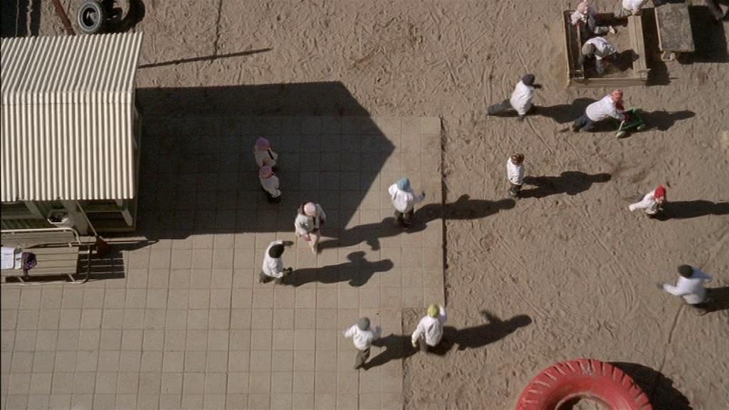 Valkoiseen paitaan puettuja lapsia päiväkodin pihamaalla ylhäältä nähtynä