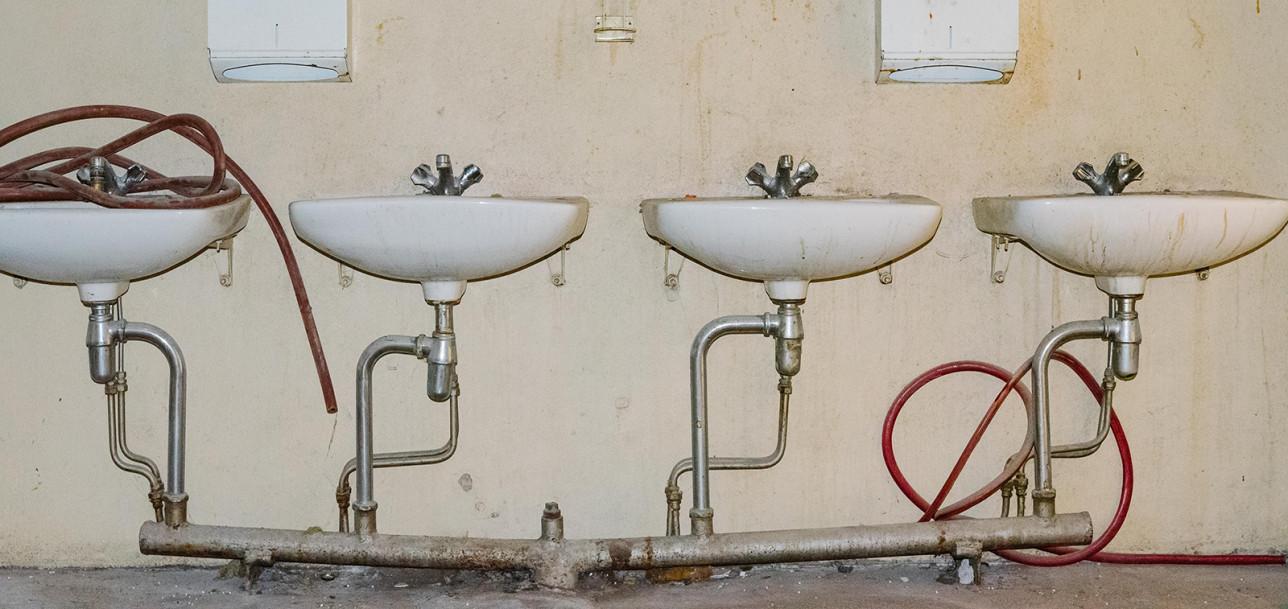 Monta käsienpesuallasta vierekkäin yhdellä seinustalla.