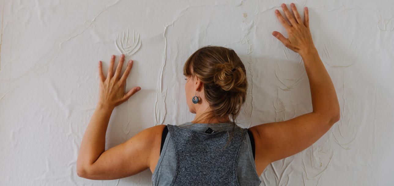 Maria Laitila tunnustelee rosoista seinäpintaa käsin.