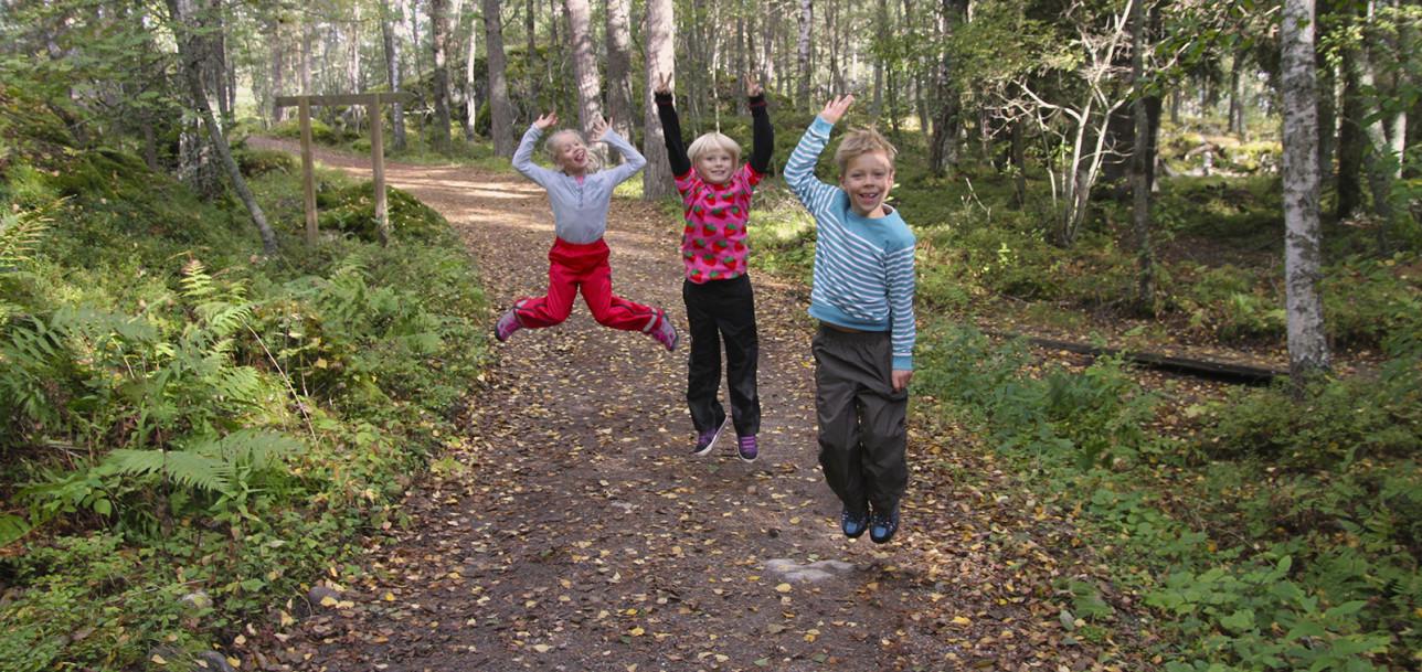 Lapset hyppäävät ilmaan metsätiellä