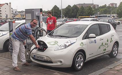 Miehet lataavat sähköautoa.