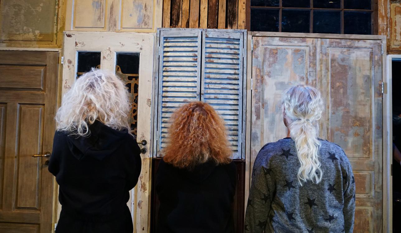 Kolme kiharahiuksista naista seisoo selin kameraan lavasteseinän edessä