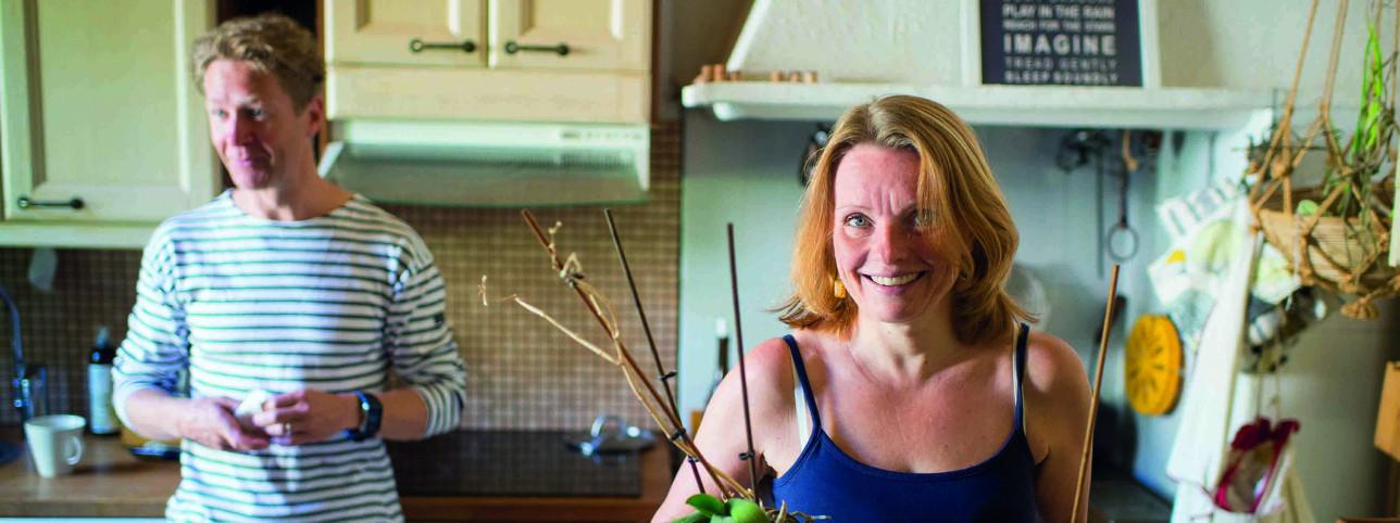 Mies ja nainen keittiössä lieden äärellä