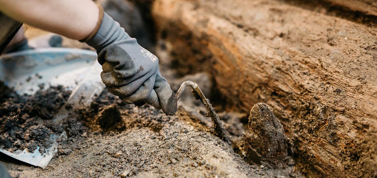 Pienellä työkalulla kaivetaan kivistä maata.