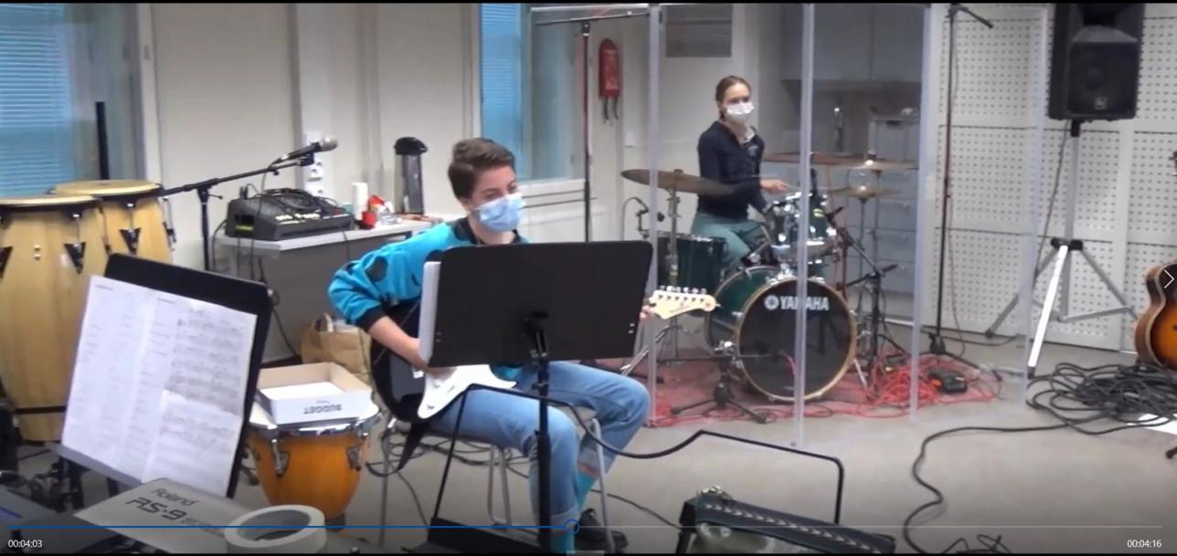 Katedralskolanin kaksi opiskelijaa soittamassa rumpuja ja kitaraa lukion musiikkiluokassa.