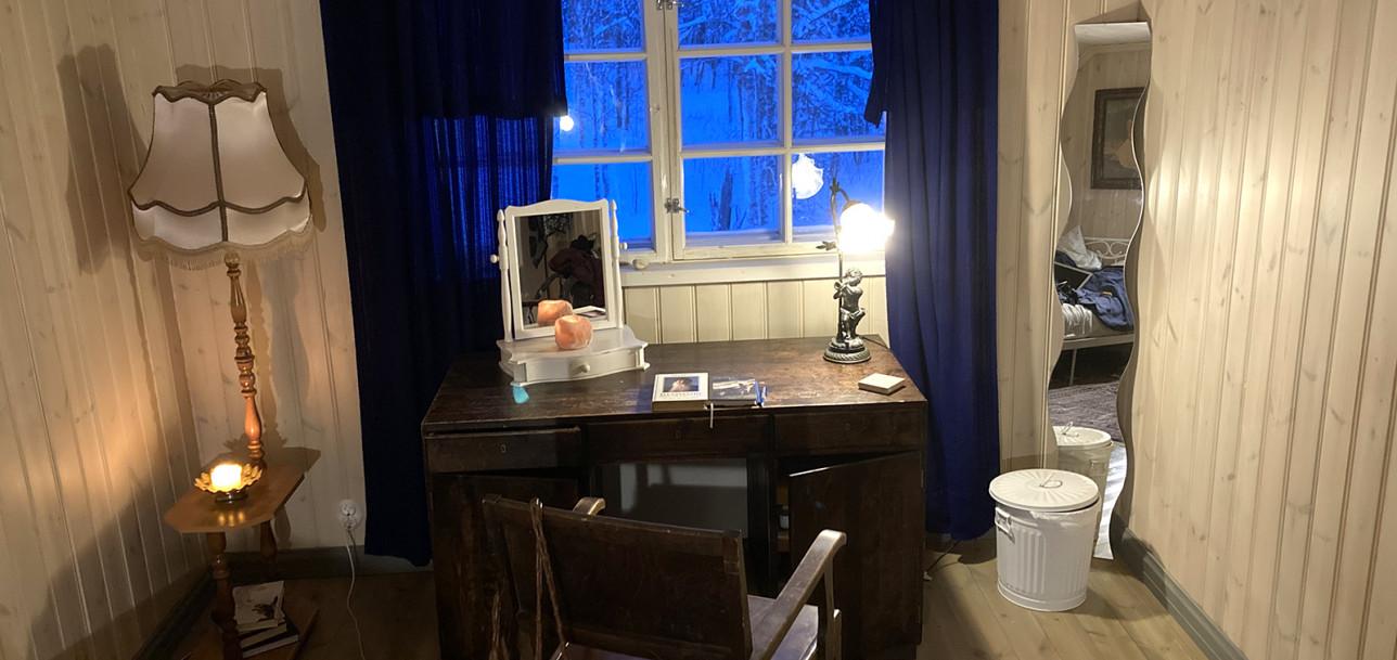 Huone, jossa ikkunan edustalla on kirjoituspöytä ja tuoli. Vasemmassa nurkassa on jalkalamppu ja pöydällä koristeellinen lamppu, jossa palaa valot. Pöydällä on valkoinen piian peili, jonka edustalla palaa kynttilä. Huoneessa on tummansiniset verhot.