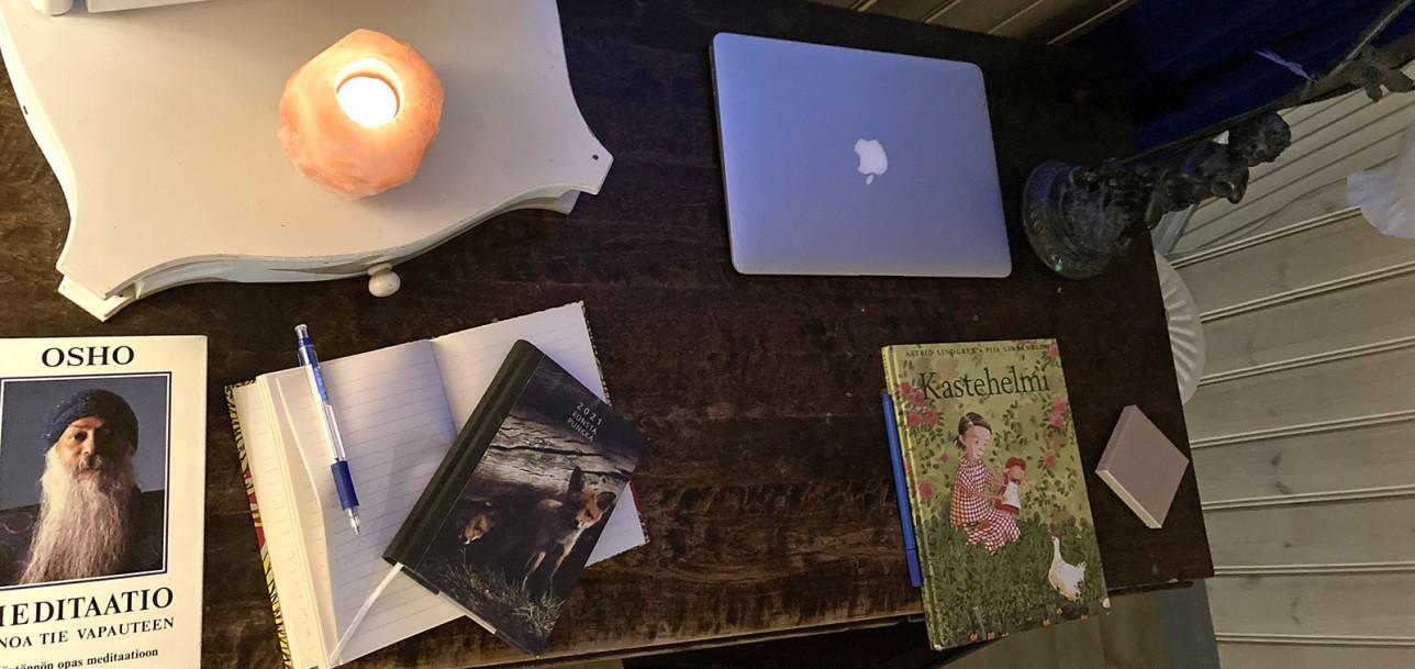 Ruskean kirjoituspöydän päällä on muun muassa piianpeili, kannettava tietokone, Astrid Lindgrenin Kastehelmi-kirja sekä muistikirja ja kynä. Piianpeilin päällä palaa kynttilä.