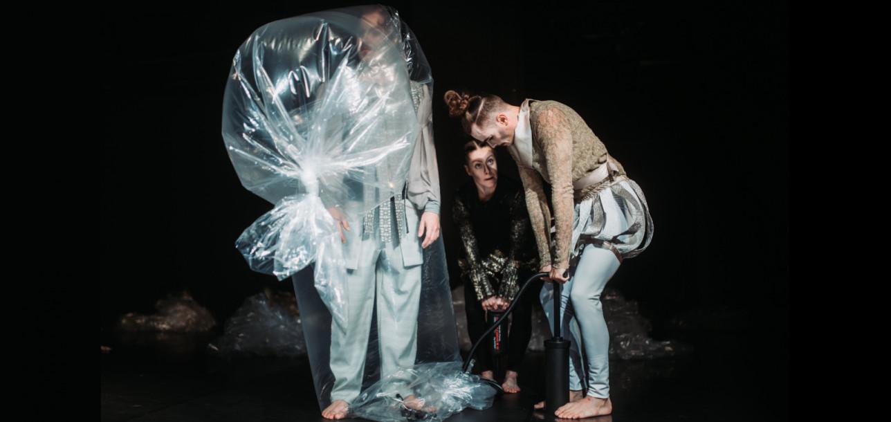 Esityksen kohtaus, jossa Don Hypnotrick on muovin sisällä ja Don Eläina ja Don Cômppu pumppaavat ilmaa muovin sisään.