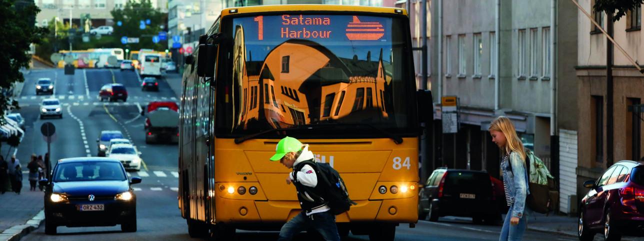 Kaksi lasta kävelee suojatiellä linja-auton edessä