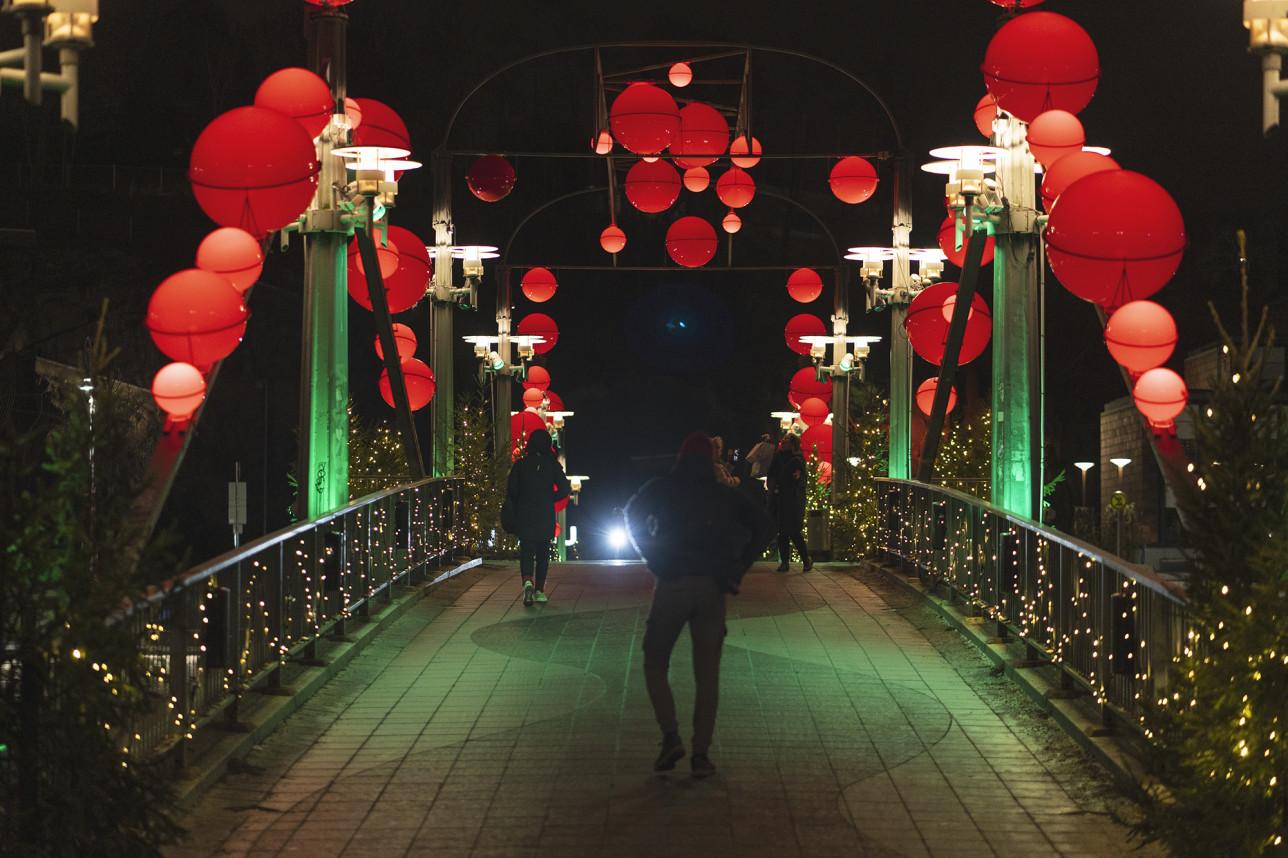 Teatterisillan kaiteissa loistavat molemmin puolin suuret pyöreät punaiset jouluvalot. Sillalla kulkee ihmisiä hämärässä illassa.