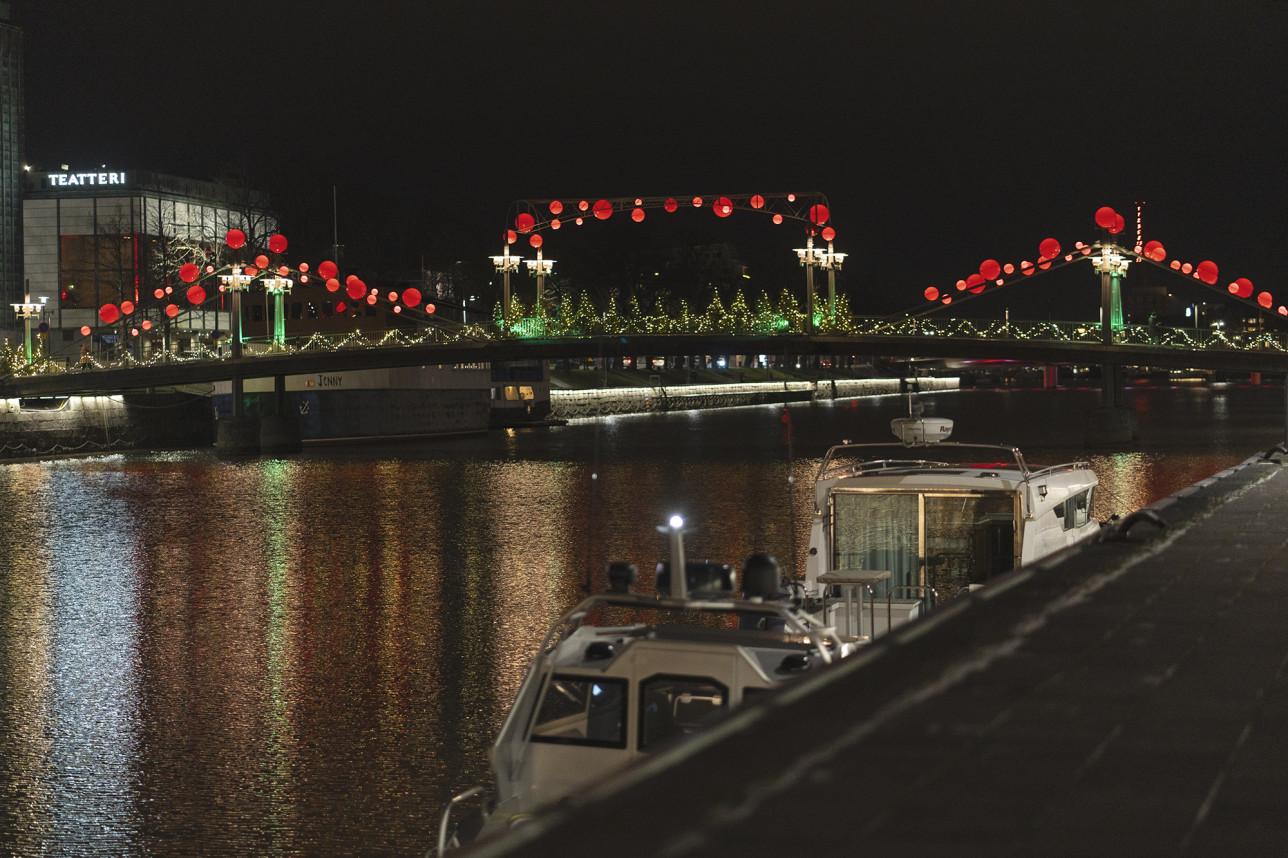 Aurajoki kimmeltää ja kaupungin valot heijastuvat siitä. Taustalla näkyy Teatterisilta, jonka kaiteissa on punaiset jouluvalot.