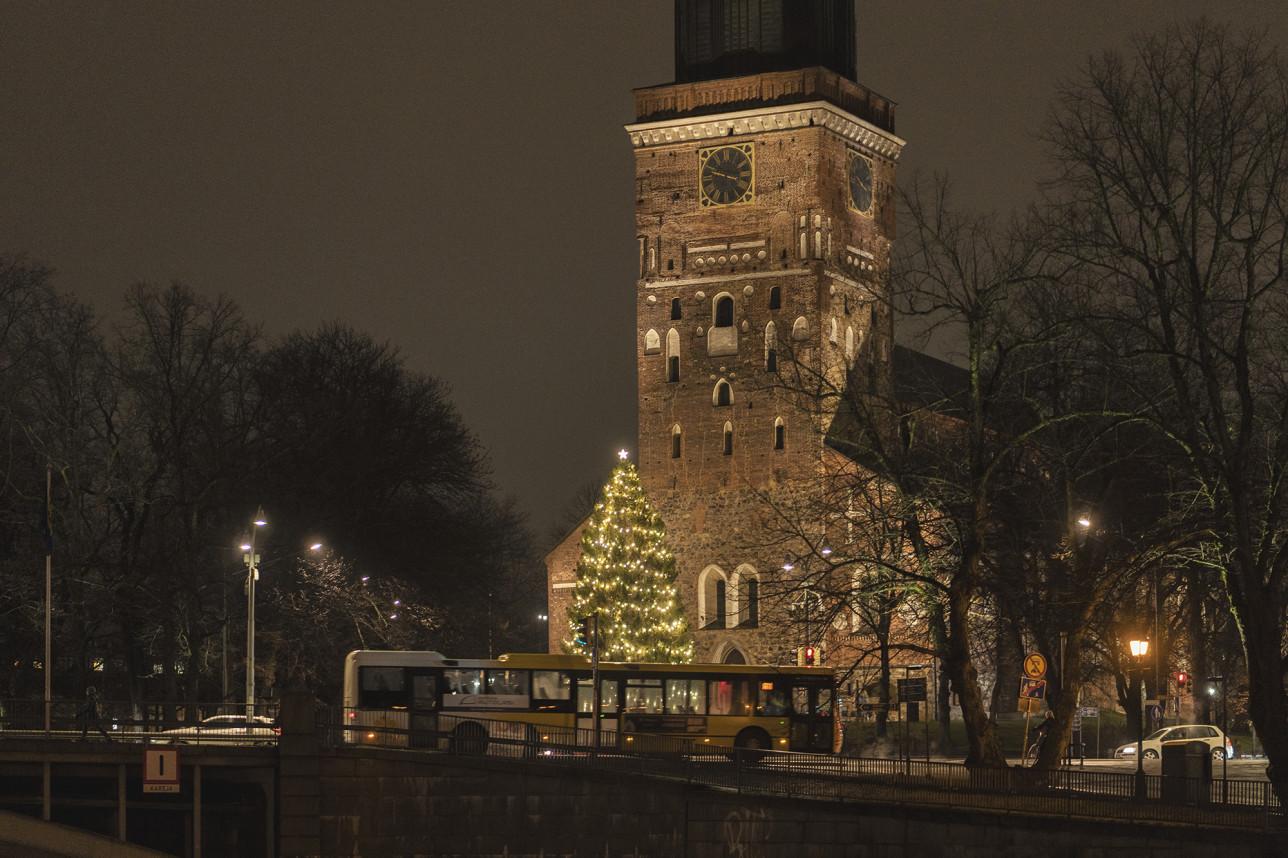Turun tuomiokirkko illalla. Sen edustalla kimmeltää lämpimästi valaistu joulukuusi. Etualalla liikenteessä oleva keltainen Föli-bussi.