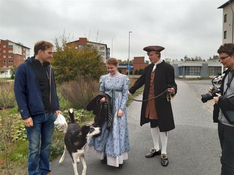 Kadulla neljä ihmistä ja mustavalkoinen pystykorvakoira. Keskellä 1700-luvun tyyliin pukeutuneet nainen vaaleansinisessä mekossa ja mies tummassa takissa, kolmikolkkahatussa ja polvihousuissa.
