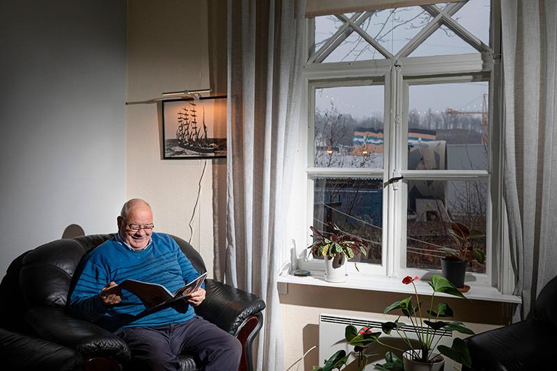 Björn Kullberg selaa valokuvakirjaa. Taustaseinällä valokuva Olivebank-aluksesta, ja ikkunasta näkyy Bore-laiva.