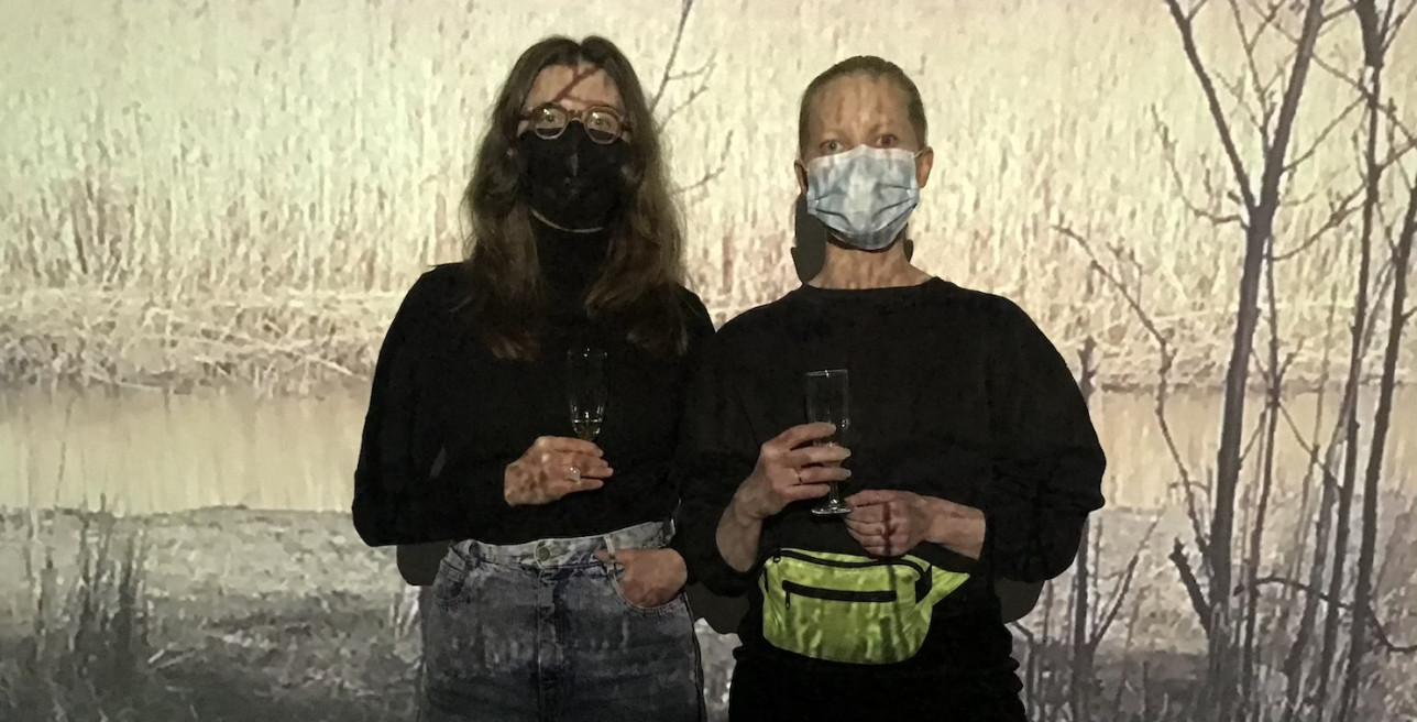 Kaksi naista seisoo seinälle heijastuvan kuvan edessä, katse kameraan päin.