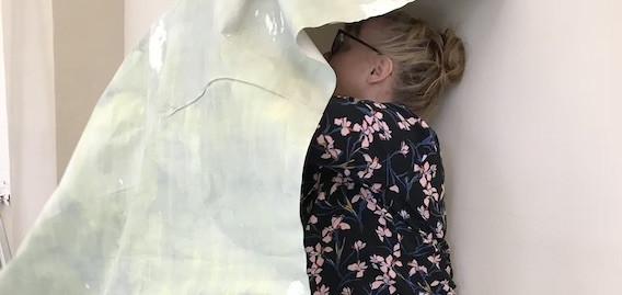 Ihminen nojaamassa seinään osittain kankaan peitossa.