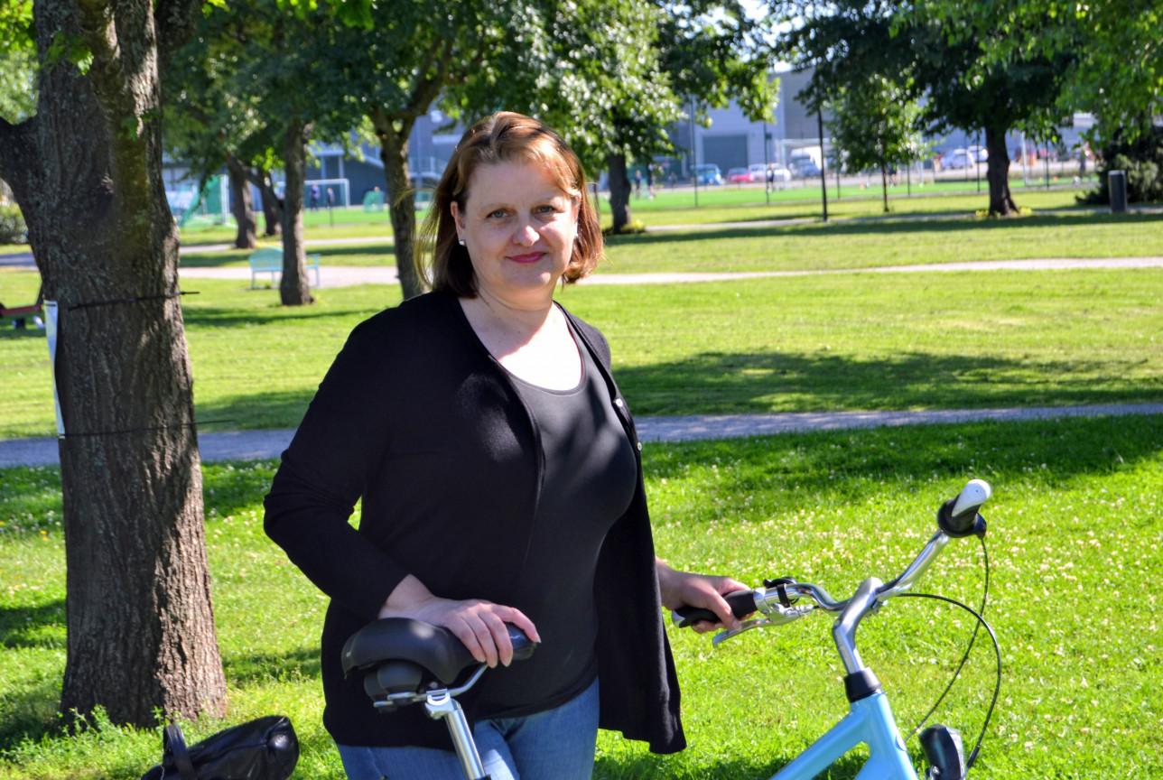 Leila Hurmerinta taluttaa pyörää nurmikolla 2