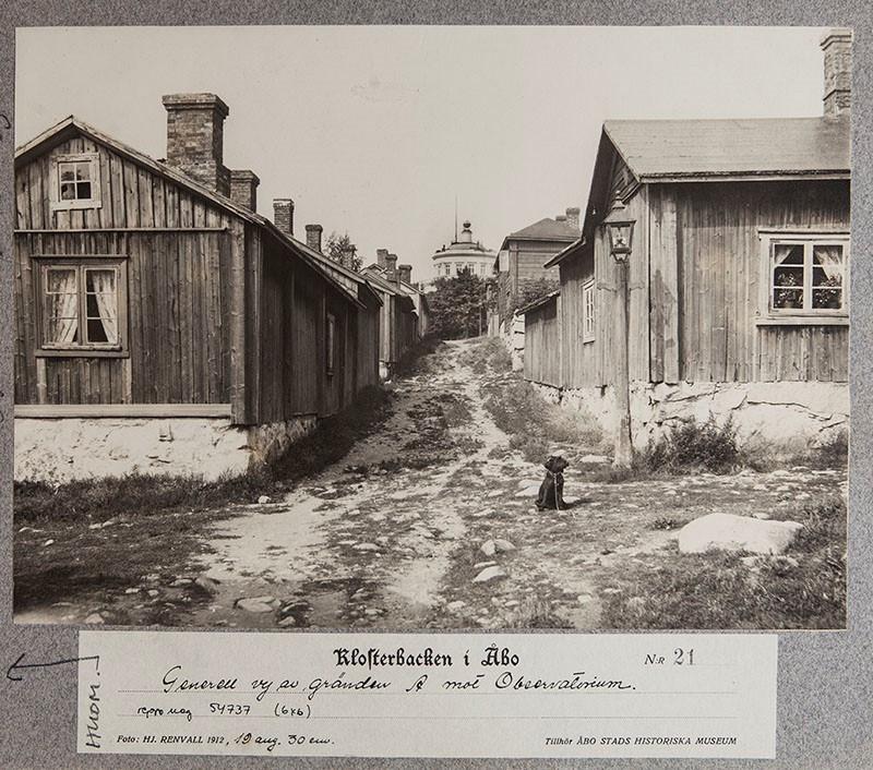 Mustavalkoinen kuva Luostarinmäestä vuodelta 1912. Kujalla istuu koira ja taustalla näkyy Tähtitorni.