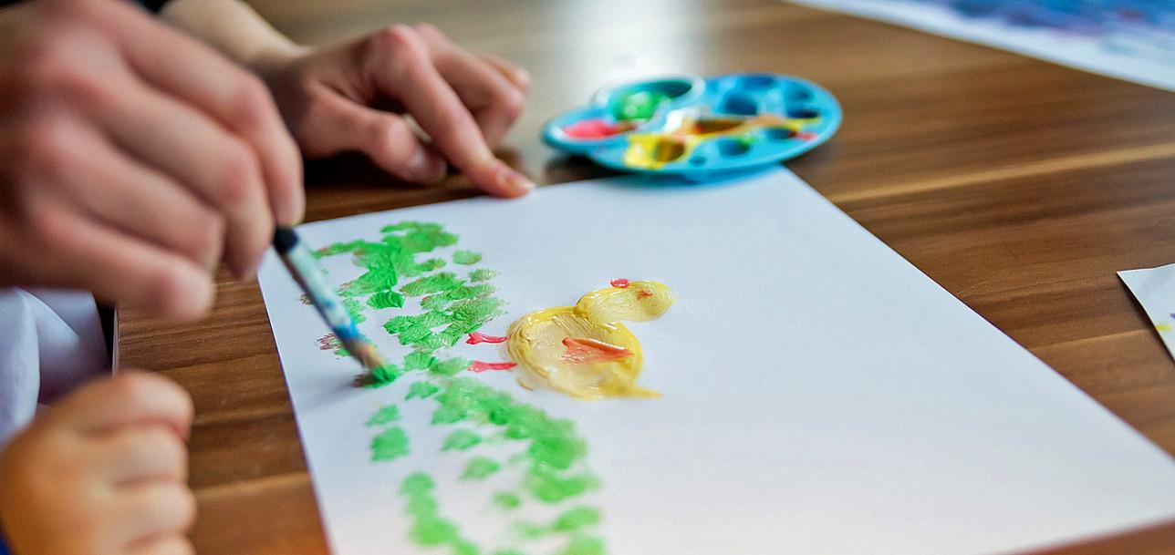 Lapsi ja aikuinen maalaavat yhdessä.