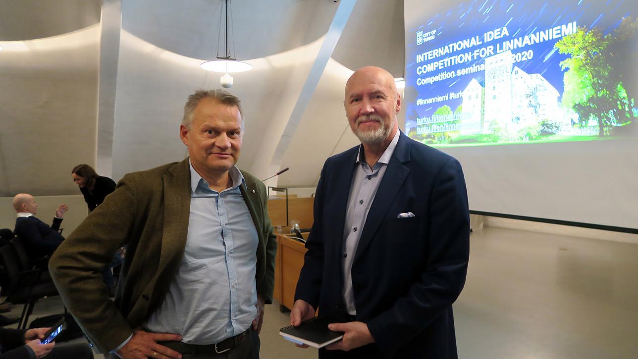 Markku Wilenius ja Timo Hintsanen, taustalla näytöllä Linnanniemen kilpailuseminaarin aloitusdia, jossa on Turun linnan kuva.