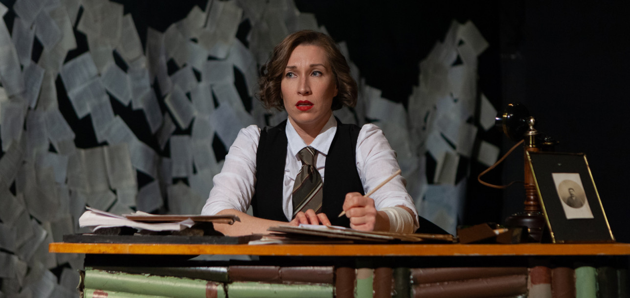 Nainen istuu kirjoituspöydän ääressä.