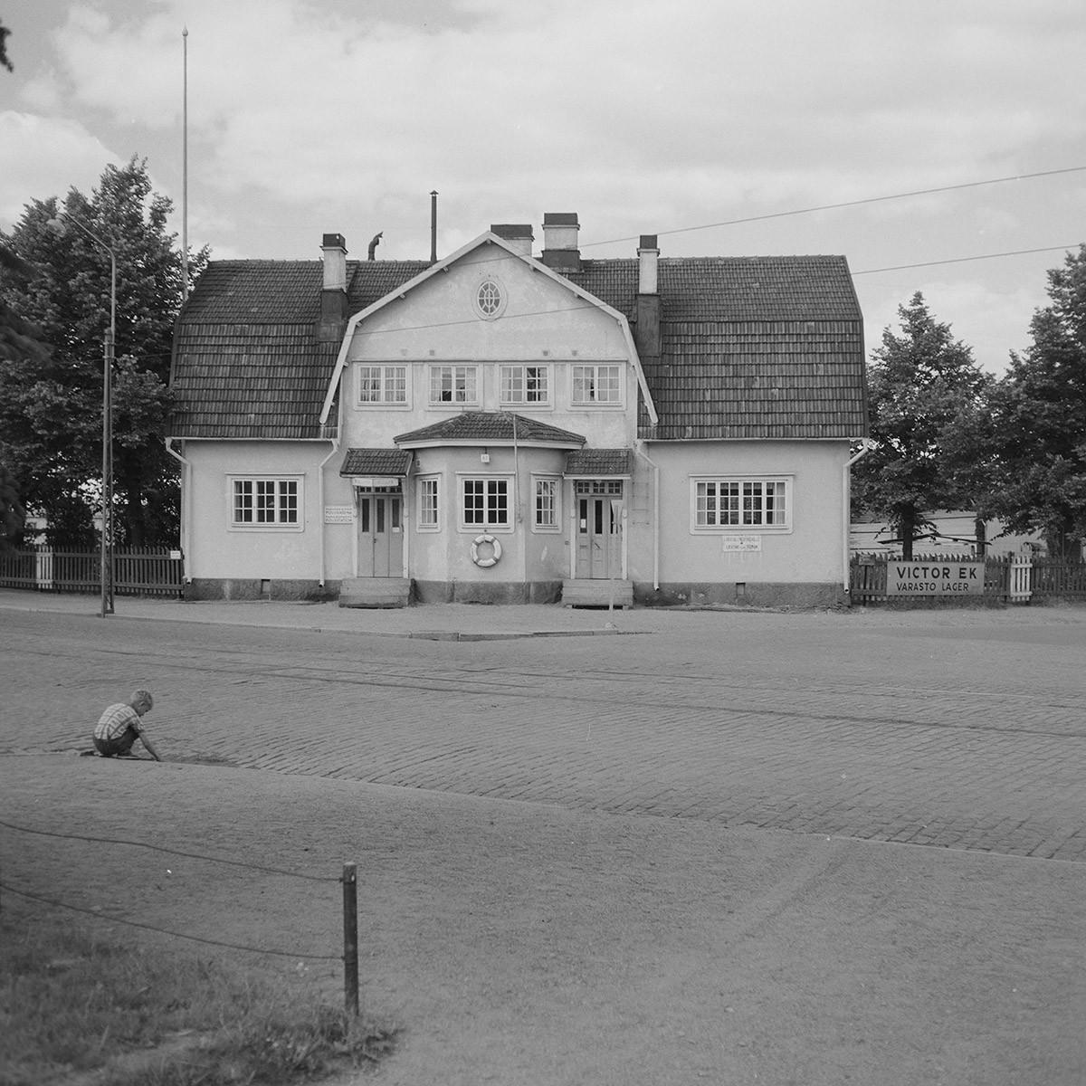 """Mansardikattoinen talo kuvattu suoraan edestä. Oikealla portinpielessä kyltti """"Victor Ek"""". Etualalla istuu kyykkyasennossa lapsi selkä kameraa päin."""