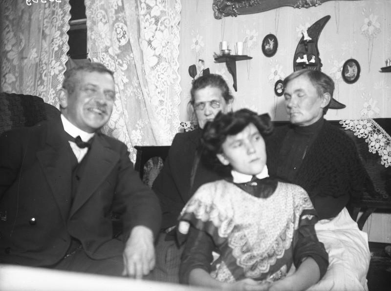 Etualalla nuori nainen katsoo sivulle pois kamerasta, hänen vieressään mies hymyilee, takana kaksi vanhaa naista.