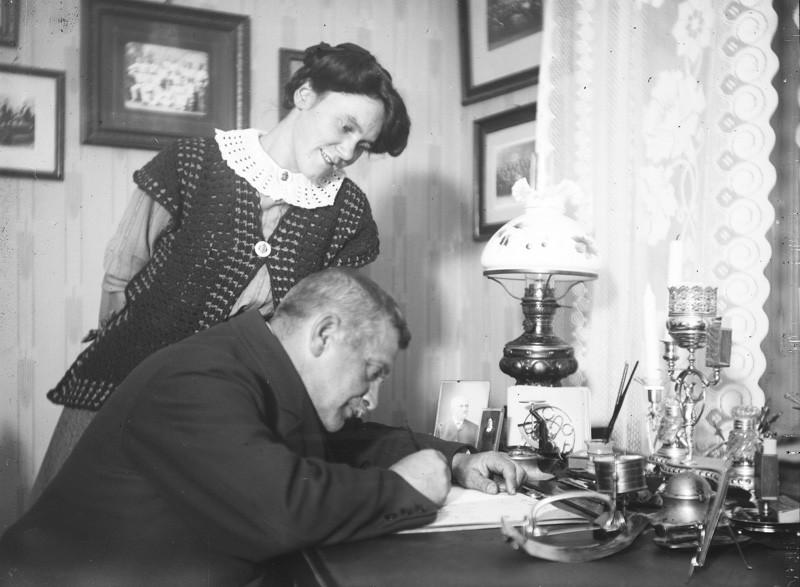 Mies kirjoittaa kirjoituspöydän ääressä, nainen seuraa vierestä.