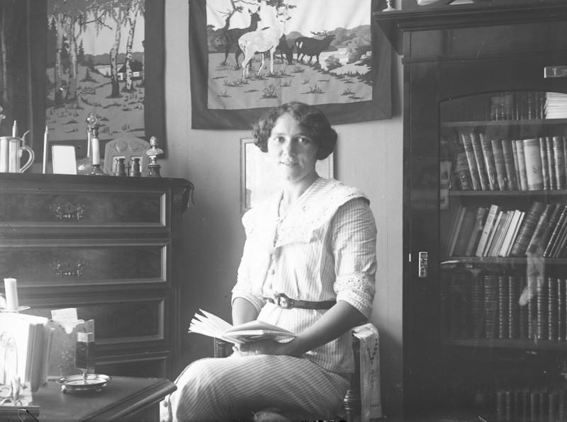 Nuori nainen kirja kädessään. Huoneessa taustalla lipasto ja kirjahylly.