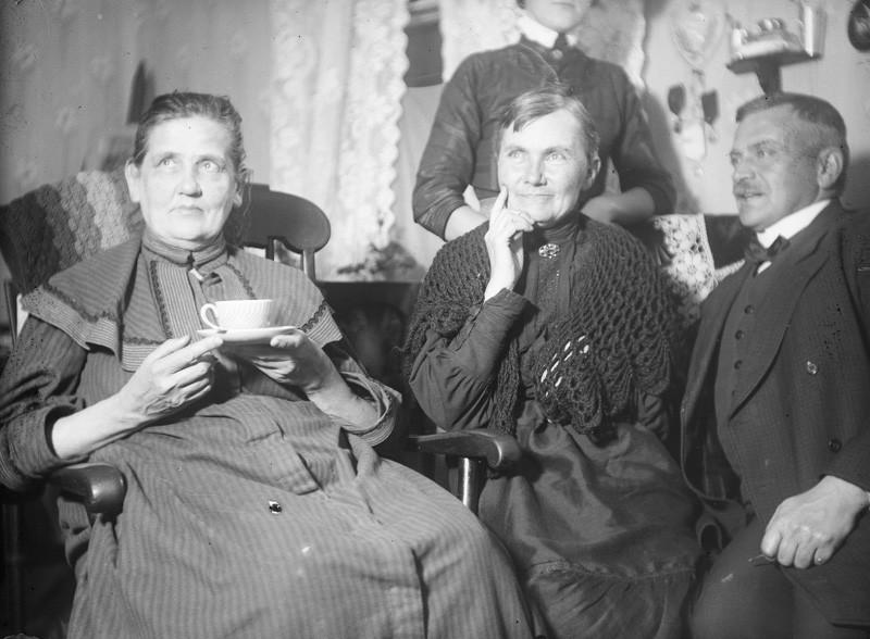Kaksi vanhempaa naista, toisella kädessä kahvikuppi. Kuvassa reunassa myös vanhempi mies ja takana nainen, jonka pää ei ole mahtunut kuvaan.