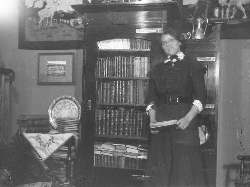 Nainen seisoo kirjahyllyn edessä kirja kädessään.