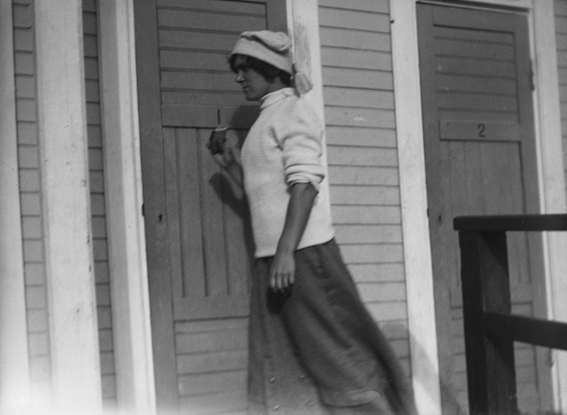Vaaleaan pitkähihaiseen paitaan ja pitkään hameeseen pukeutunut nainen kuvattuna melkein koko pituudelta sivultapäin. Päässä tupsulakki.