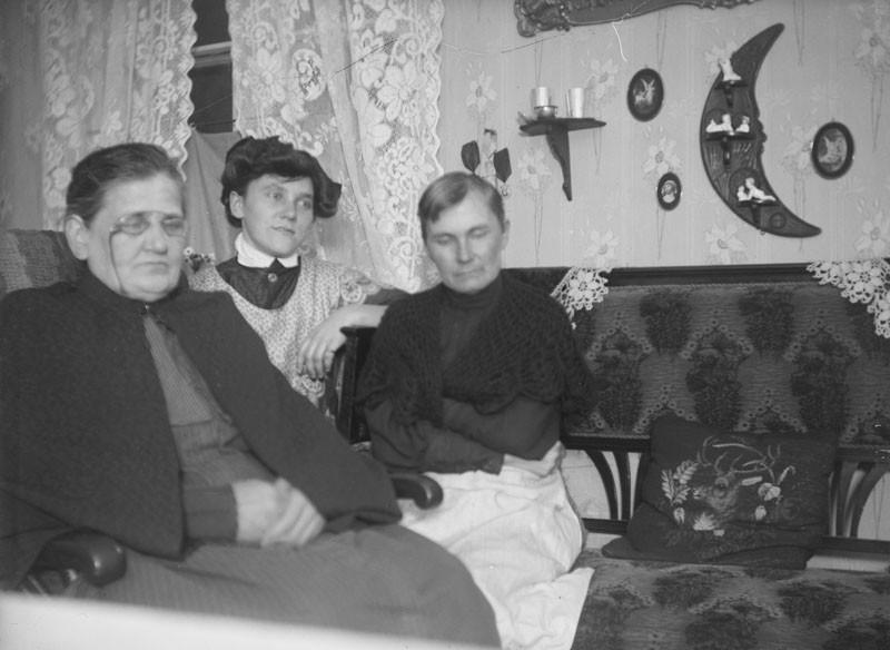 Nuori nainen ja kaksi vanhaa naista istumassa sohvilla.