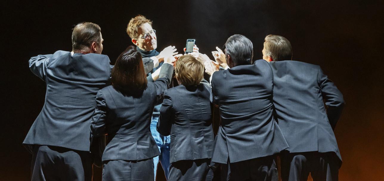 Viisi henkilöä harmaissa puvuissa tavoittelee yhden henkilön kädessään pitelemää matkapuhelinta.